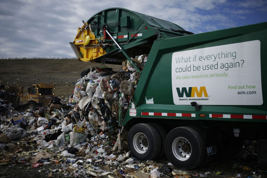 A Waste Management, Inc. garbage truck dumps a load of trash at the Waste Management Skyline Landfill in Ferris, Texas, U.S., on Monday, Oct. 24, 2016. Waste Management is scheduled to release their next quarterly earnings on October 26. Photographer: Luke Sharrett/Bloomberg